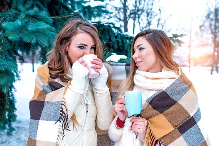 Two girls girlfriends in winter on street, warm themselves in warm plaid, drink hot drinks, coffee tea, happy talk and relax on winter holidays, background snow trees spruce