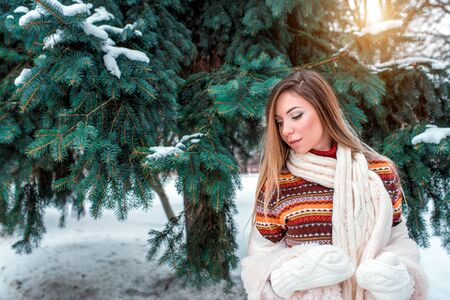 Beautiful girl sweater scarf, winter snowy park, background spruce white snow, happy warms herself warm jacket, relaxes winter resort on weekend. Emotions pleasure enjoyment. Free space for text Stok Fotoğraf