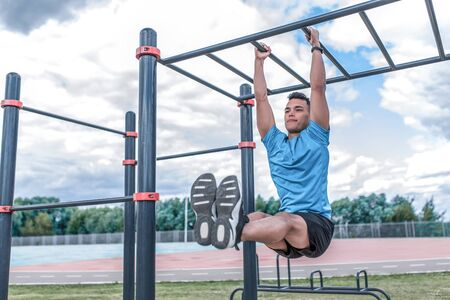 Male athlete, training abdominal muscles, exercise on press, raising legs crossbar. In summer spring in city. Active lifestyle, workout, fitness fresh air. Motivation Blue t-shirt, cloud background