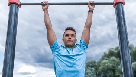 male athlete pulls himself up on bar. In summer spring in city. Active lifestyle, workout, fitness in fresh air. Motivation for sports. Blue t-shirt, cloud background