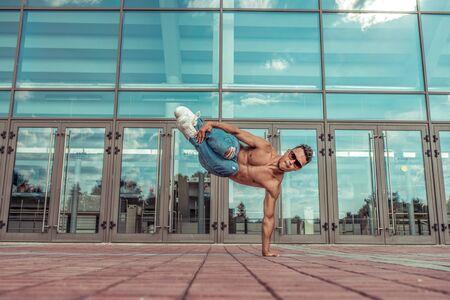 Man athlete, guy dancer summer city. Glasses on background glass windows. Tanned torso press break dance style fast fitness sport hip hop in motion. Urban culture, street dance. Acrobatic exercises
