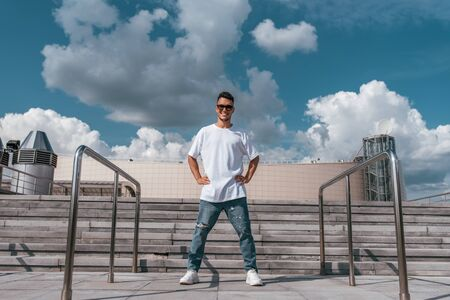 Male athlete, guy dancer in the summer in city. Standing in a pose ready to dance break dance. Happy smiles, in a T-shirt, jeans and sneakers. Background concrete stair clouds 免版税图像
