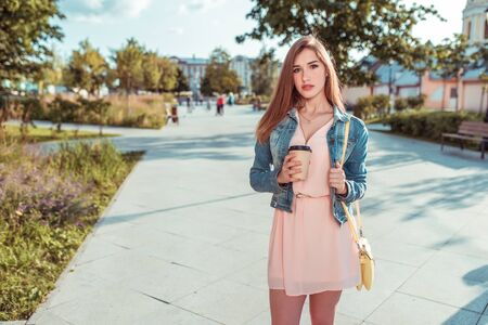 beautiful girl student standing city summer, holding cup coffee tea, yellow handbag, waiting for friends girlfriends, long hair, tanned slim figure. Pink dress casual makeup. Free space for text Фото со стока