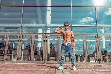 Man athlete, guy dancer summer city. Glasses background glass windows. Tanned inflated torso abs and biceps. Fashionable modern break dance style, fitness sport hip hop. Urban culture, street dance
