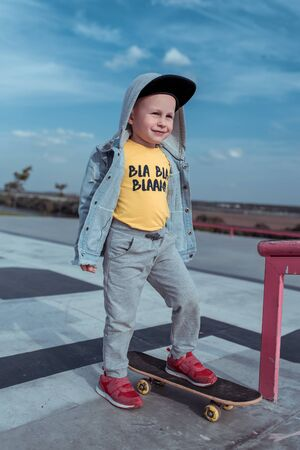 Little boy 3-5 years old, in autumn summer in city, skateboard training, happy smiling, casual wear denim jacket, baseball cap. The boy is riding on board. Stock Photo