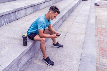 male athlete, tanned man, summer city, resting his hands with mobile phone, listening music headphones, bottle protein water, fitness workout morning joggings. Free space for motivation text Фото со стока