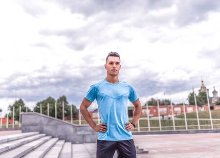 Confident and strong male athlete, summer city, trainer stares intently, background is blue clouds, free space for motivation text, fitness workout workout. Sportswear t-shirt, fitness bracelet