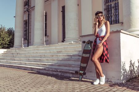 Girl in summer in city, calling on cell phone, free space for text. Skateboard, board for riding, resting listens to message bell. Tanned figure of beautiful woman in baseball cap and sunglasses Фото со стока