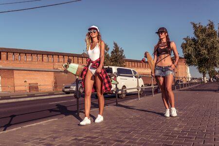 Two girls girlfriends summer walk city longboard skateboard. Resting weekend walk, sports fitness, girls. Background road tree, casual wear, free space for text