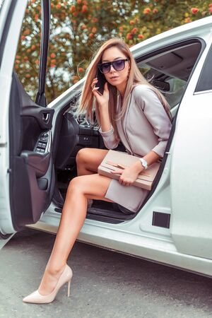 Beautiful business lady woman gets out car, calls phone hand smartphone, beige clutching handbag, sunglasses, summer city, business class car, VIP taxi, tanned legs with high heel shoes