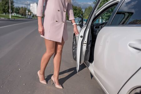 A woman in a pink suit opens car door, in the summer in the city, business taxi, tanned skin, long legs, high-heeled shoes.