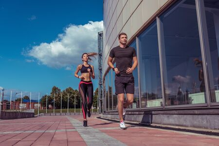 Athletic couple man and girl in summer city, run on morning run, burning calories, cardio fitness training day and morning. Healthy lifestyle style. Sportswear, friends and relationships are paired