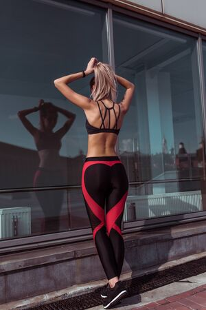 Beautiful athletic and tanned athlete girl straightens her hair hairstyle, does pigtail tail, summer city background of glass windows, fitness motivation. Sportswear Leggings Top. Back view