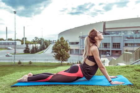 beautiful and athletic figure of a girl, in the summer in city on a yoga mat, flexibility and plasticity training, active lifestyle, morning gymnastics in nature, sportswear, long hair
