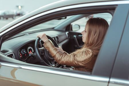 Girl driving car, holds hand, parking shopping center, takes a turn, close-up of the window and door of the car. Leather jacket long hair, emotions of comfort from driving a car