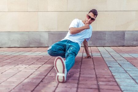 athlete man dancer in a white T-shirt, jeans and glasses, dancing, summer in city, background wall, active hip hop, youth lifestyle, pensive, thinks and thinks street artist style