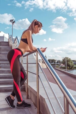 Beautiful tanned girl in sportswear top leggings, resting after jogging in the morning in city, holding a phone, online message application in a smartphone, online training pulse and calories Фото со стока