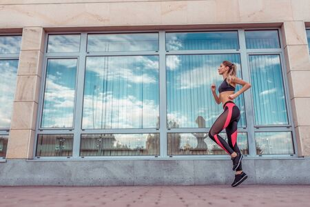 Athletic woman runs jogging morning afternoon, glass windows background, summer training in city. Sportswear Leggings Top. Motivation for fitness workout lifestyle. Free space for text Zdjęcie Seryjne