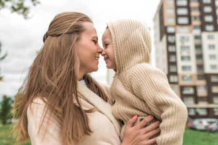 Woman mom happy smiling with little boy son 4-5 years old, autumn in the city, building background, casual clothes. Having fun playing, positive emotions. Beige sweater with a hood.