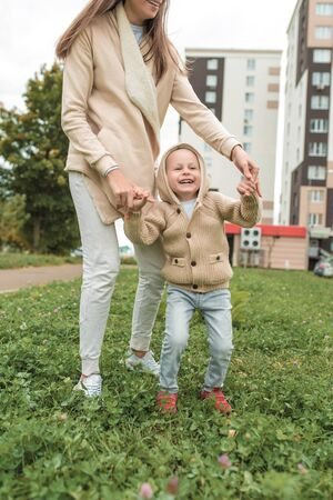 Woman mom plays with little boy son 3-5 years old, in autumn in city, background of building, casual clothes. Having fun playing laughing rejoicing, positive emotions. Beige sweater with a hood.