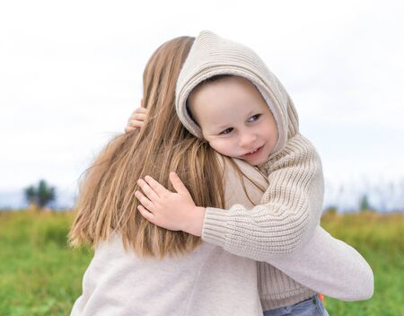 Little boy 3-5 years old, hugs his mother woman in warm sweater with hood, happy smiling. In summer autumn park. Emotions of love care understanding and trust and support. Zdjęcie Seryjne