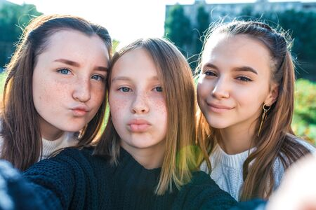 Three girls schoolgirls girlfriends kissing video camera smartphone. They take pictures themselves with camera. They transmit video call, online app Internet. In summer city nature. Autumn sweaters