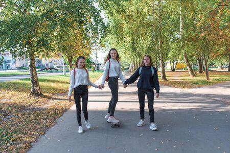 Schoolgirls teenagers girls, 3 girlfriends ride skateboard, have fun in summer in park, background trees, autumn leaves, happy having fun, relaxing after school, returning home