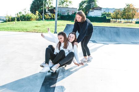 Schoolgirls teenagers girls, 3 girlfriends ride skateboard, have fun, happy have fun, play, relax after school, emotions of joy and delight of pleasure. In summer city nature. Autumn warm sweaters