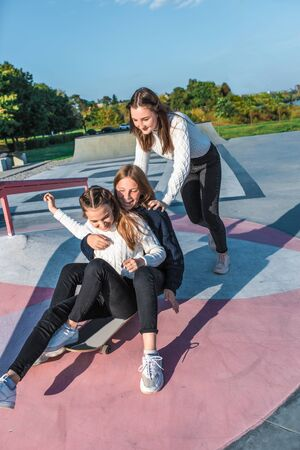 Schoolgirls teenagers girls, 3 girlfriends ride skateboard, Autumn warm sweaters have fun, happy have fun, play, relax after school, emotions of joy and delight of pleasure. In summer city nature. Zdjęcie Seryjne