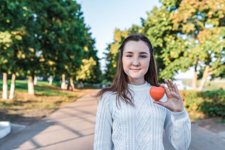 Teenage girl schoolgirl, teenager white sweater autumn in city background trees road, warm sweater, in hands of toy heart, gift and help, donation and love, free space for text