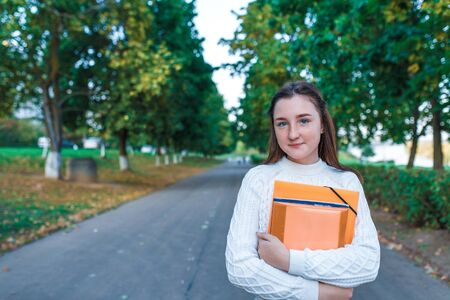 Teenage girl schoolgirl, teenager white sweater summer city, warm sweater, hands notebooks books and folders, smiling happy, after lessons school institute free space text. background trees road Zdjęcie Seryjne