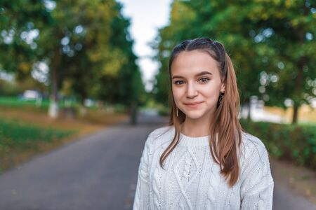 Girl teenager schoolgirl in summer in autumn city, background trees road. Free space for text. Happy smiling close-up portrait. White sweater. Emotions happiness, fun relaxation after school 스톡 콘텐츠