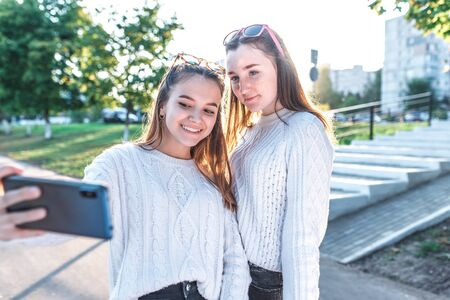 Schoolgirls teenagers girls, 2 girlfriends take pictures themselves on phone, happy smiling have fun, record video, video call, have fun in city in summer, happy play, relax after school