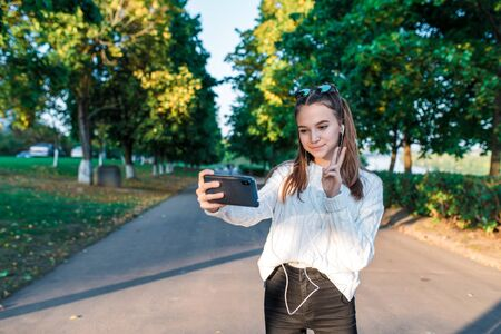 Teenage girl schoolgirl, teenager headphones taking pictures themselves phone, happy smiling having fun, recording video, video call, autumn summer city, white sweater, jeans. Background trees road