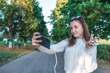 Teenage girl schoolgirl, happy smiling having fun, recording video, video call, teenager headphones taking pictures themselves phone, autumn summer city, white sweater, jeans. Background trees road