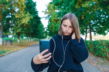 teenage girl schoolgirl, teenager with headphones taking photos themselves phone, serious girl listens conversation, recording, video call, autumn summer city, black sweater. Background trees road