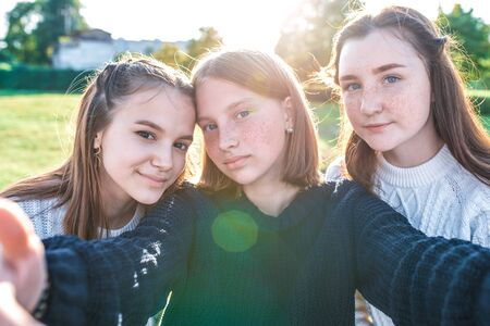 Three girls schoolgirls girlfriends, close-up, taking pictures themselves camera phone. Video recording, video call, online application Internet. In summer in city in nature. Autumn warm sweaters