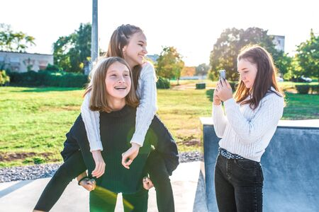 Three girls schoolgirls girlfriends, teenagers having fun taking pictures phone. Video recording. In summer city nature fall, happy people warm sweaters play, relax after school emotions joy delight Stok Fotoğraf