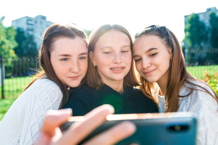 Three girls schoolgirls girlfriends smiling happy take photo on smartphone. Selfies on phone, social networks, online application, video call to Internet. In summer in city in nature