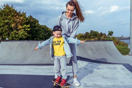 Mutter Frau glücklicher kleiner Junge Sohn 3-5 Jahre alt, lernt Skateboard zu fahren, Sommer Herbst im Stadtpark Spielplatz. Skateboard, Freizeitkleidung. Unterstützung beim Gleichgewichtstraining. Emotionen der Freude Spaß.