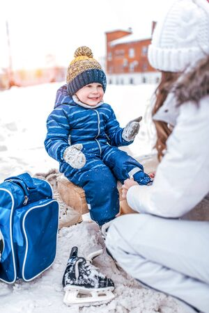 mother helps woman, winter, put on shoes skates, son little boy 4-5 years old, train learn skate, warm clothes, relax on weekend. Background snow drifts ice rink. Happy smiling cheerful and joyful.