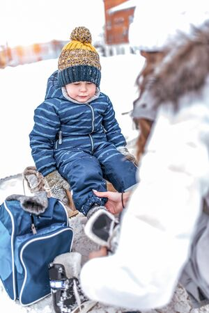 mother helps woman, in winter, put on shoes skates, son little boy 4-5 years old, train and learn to skate, warm clothes, relax on weekend. Background snow drifts ice rink. Bag hat blue jumpsuit.