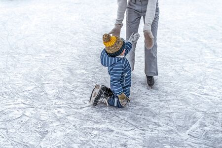 parent helps to get up and rise winter, son little boy 4-5 years old, train learn to skate, in warm clothes, relax on weekend. Background snow drifts ice rink. Help support learning. Free space text.