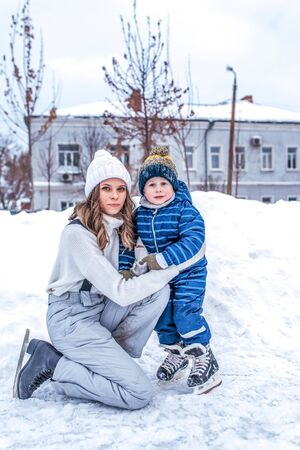 young mother helps woman in winter, her son a little boy 4-5 years old, train and learn to skate, in warm clothes, relax on weekend. Background snow drifts ice rink. Help and support in learning.