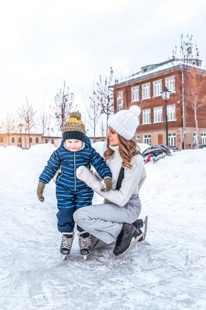 Mom is a woman in winter with her son little boy 4-5 years old, studies and trains to skate, in warm clothes, happy smiles and relax on weekend. Background snow drifts ice rink. Banco de Imagens