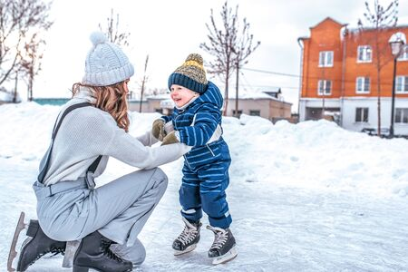 Mom woman winter with her son, little boy 4-5 years old, studying and training to skate, warm clothes, happy smiling, relax on weekend. Background snow drifts ice rink. Free space for text.