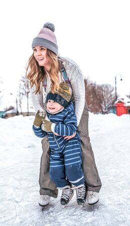 woman in winter with her son, a little boy 4-5 years old, train and learn to skate, in warm clothes, happy smiling, relax on weekend. Background snow drifts ice rink. Emotions of joy and laughter.
