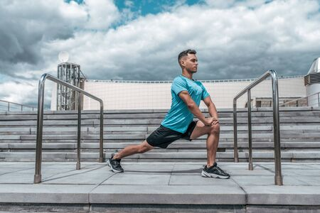 Male athlete doing stretching before training, lunges, jogging before jogging, summer city, cloud steps background. Active youth lifestyle, fitness workout in nature.