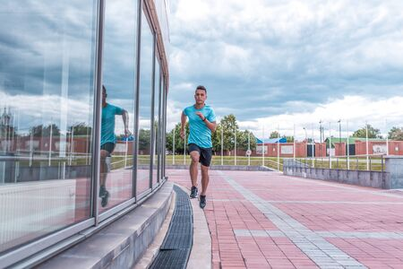 male athlete runs morning run full length, summer city, background is building. Active youth lifestyle, fitness workout in nature. Free space for text strength motivation. Zdjęcie Seryjne