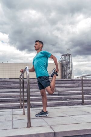 male athlete does stretching before jogging workout, in the summer in the city, the background of the cloud steps. Active youth lifestyle, fitness workout in nature. Zdjęcie Seryjne